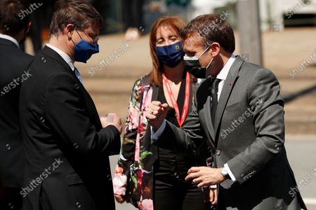 French President Emmanuel Macron, right, bumps fists with European Commissioner for An Economy that Works for People Valdis Dombrovskis, left, as he arrives for an EU summit at the Alfandega do Porto Congress Center in Porto, Portugal, . European Union leaders are meeting for a summit in Portugal on Friday, sending a signal they see the threat from COVID-19 on their continent as waning amid a quickening vaccine rollout. Their talks hope to repair some of the damage the coronavirus has caused in the bloc, in such areas as welfare and employment