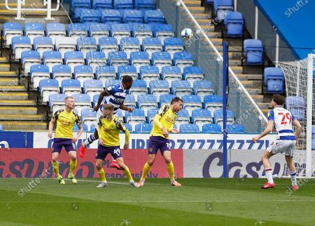 Yakou Meite of Reading leaps to head the ball over Scott High, Lewis O'Brien and Richard Keoghof Huddersfield Town to score his sides 2nd goal in the 26th minute to make it 2-1; Madejski Stadium, Reading, Berkshire, England; English Football League Championship Football, Reading versus Huddersfield Town.