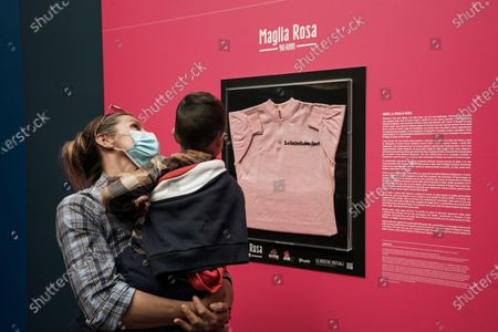 Stock Photo of Visitors look at the Maglia Rosa of Italian cycling legend Fausto Coppi, exhibited at the Museo Egizio in Turin, Italy, 07 May 2021. The Giro d'Italia overall leader's pink jersey celebrates its 90th anniversary. The 104th edition of the Giro d'Italia will take place from 08 May through 30 May 2021.