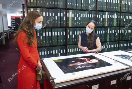 Britain's Kate, Duchess of Cambridge views a photo of Captain Tom Moore alongside Curator Magda Keaney during a visit to the archive in the National Portrait Gallery in central London, to mark the publication of the book 'Hold Still