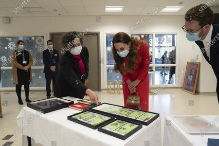 """Britain's Kate, Duchess of Cambridge with Catsou Roberts, Director of Vital Arts for Barts Health NHS Trust during a visit to Royal London Hospital in Whitechapel, east London, to mark the publication of the book """"Hold Still"""