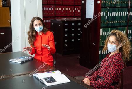 Catherine Duchess of Cambridge talks to 'Hold Still' entrant Naz Maleknia (right) during a visit to the archive in the National Portrait Gallery in central London to mark the publication of the 'Hold Still' book.