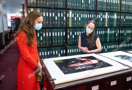 Catherine Duchess of Cambridge views a photo of Captain Tom Moore alongside Curator Magda Keaney during a visit to the archive in the National Portrait Gallery in central London to mark the publication of the 'Hold Still' book.