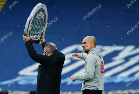Stock Photo of Manchester City Manager Pep Guardiola points as fourth official Jon Moss holds up the Hublot substitutes board