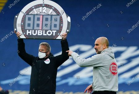 Stock Image of Manchester City Manager Pep Guardiola points as fourth official Jon Moss holds up the Hublot substitutes board