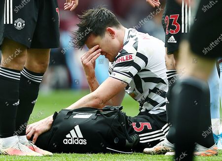 Harry Maguire of Manchester United looks dejected with an injury