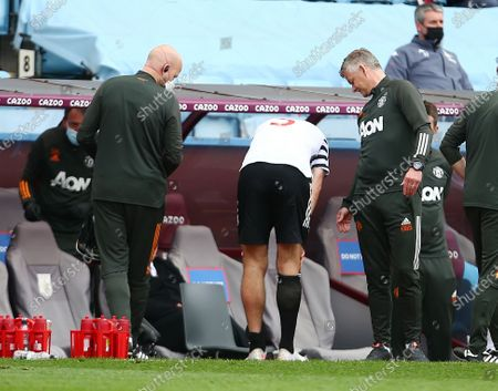 Harry Maguire of Manchester United leaves the game through injury next to manager Ole Gunnar Solskjaer