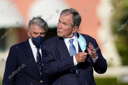 Stock Photo of Former President George W. Bush takes off his mask in accordance with tournament protocol, as he arrives to speak before the opening ceremony of the Walker Cup golf tournament, which starts tomorrow, at Seminole Golf Club in Juno Beach, Fla
