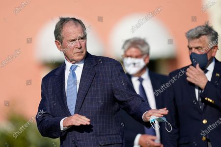 Former President George W. Bush gestures as he arrives to speak before the opening ceremony of the Walker Cup golf tournament, which starts tomorrow, at Seminole Golf Club in Juno Beach, Fla