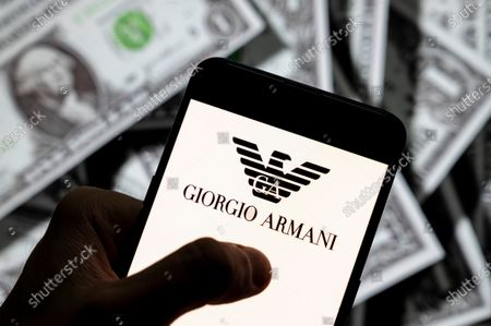 In this photo illustration the Italian luxury fashion brand Giorgio Armani logo seen displayed on a smartphone with USD (United States dollar) currency in the background.