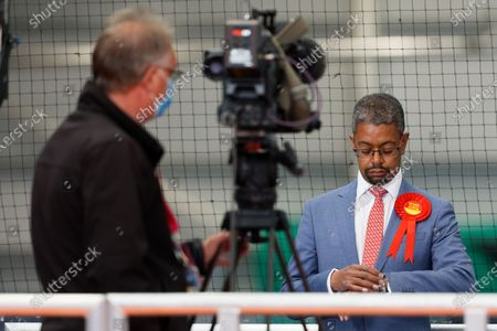 Vaughan Gething, Minister for Health and Social Services checks the time during a television interview at the ballot count