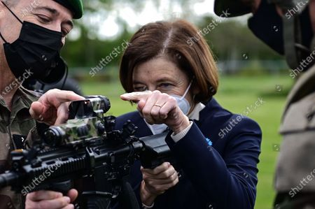 French Defence Minister Florence Parly (C) holds a machine gun during a visit to the military camp of Satory in Versailles-Satory, west of Paris, France, 07 May 2021.