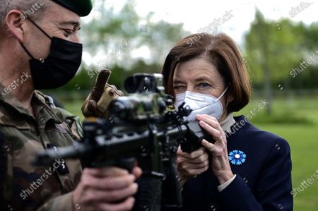 French Defence Minister Florence Parly (R) holds a machine gun during a visit to the military camp of Satory in Versailles-Satory, west of Paris, France, 07 May 2021.