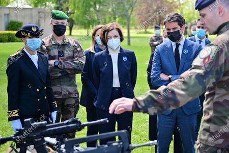 French Defence Minister Florence Parly (C) and French Secretary of State and Government's spokesperson Gabriel Attal (2-R) listen to explanations on a machine gun during a visit to the military camp of Satory in Versailles-Satory, west of Paris, France, 07 May 2021.
