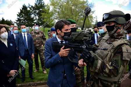 French Secretary of State and Government's spokesperson Gabriel Attal (C) holds a machine gun during a visit with French Defence Minister Florence Parly (L) to the military camp of Satory in Versailles-Satory, west of Paris, France, 07 May 2021.