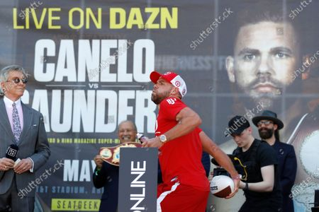 Announcer Michael Buffer, left, looks on as Billy Joe Saunders, center, throws a football into the crowd before his weigh-in, in Arlington, Texas. Saunders fights Canelo Alvarez on Saturday, May 8, 2021, for the unified super middleweight world championship