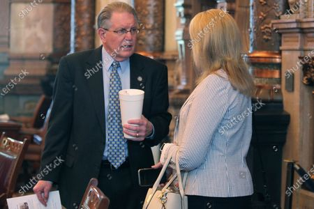 Stock Image of Kansas state Sens. Mike Thompson, left, R-Shawnee, and Alicia Straub, R-Ellinwood, talk ahead of the Senate's session, at the Statehouse in Topeka, Kan. Thompson is not satisfied with a ban on COVID-19 vaccine passports being inserted into budget legislation, arguing that it's not strong enough