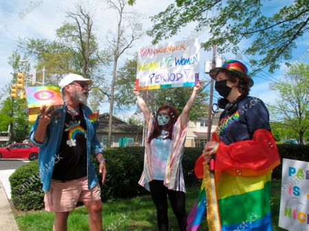 Brian Kaufman, left, Charlie Milana, center, and Emily Crowley, right, of the Philly Metro Activism Network conduct a protest in Neptune N.J., against a school vice principal who was filmed tossing beer at people who were videotaping his wife's rant against a transgender woman's use of a public restroom at an outdoor restaurant in Galloway Township N.J. in April