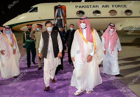 Stock Image of In this photo released by Saudi Royal Palace, Saudi Crown Prince Mohammed bin Salman, right, meets Pakistan's Prime Minister Imran Khan, at Riyadh international airport, Saudi Arabia