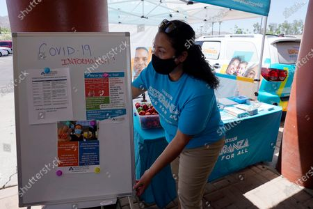 Stock Photo of Sonia Lorenzana, of UnidosUS, sets up an informational tent to increase efforts to bring more vaccine doses into Latino neighborhoods at a local shopping plaza, in Phoenix. Arizona Democrat Rep. Ruben Gallego said he is helping organize vaccination events in Latino neighborhoods, including one May 15 at a west Phoenix high school