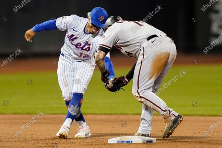 Arizona Diamondbacks' Asdrubal Cabrera, right, playfully tries to force the ball from the mitt of New York Mets shortstop Francisco Lindor (12) after he was tagged out at second while attempting to extend his single during the ninth inning of a baseball game, in New York