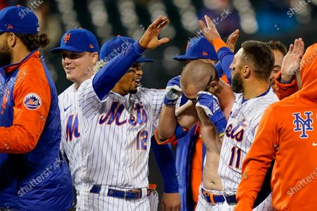 New York Mets' Francisco Lindor (12) celebrates with Patrick Mazeika, center right, who had his jersey removed by his teammates as they celebrate after Pete Alonso scored the winning run against the Arizona Diamondbacks on a grounder by Mazeika in the 10th inning of a baseball game, in New York