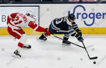 Columbus Blue Jackets forward Cam Atkinson, right, reaches for the puck next to Detroit Red Wings defenseman Dennis Cholowski during the second period of an NHL hockey game in Columbus, Ohio
