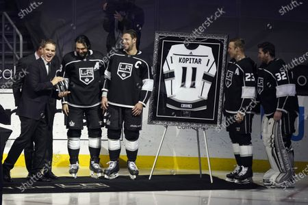Los Angeles Kings center Anze Kopitar, third from left, smiles at team president Luc Robitaille, far left, as Kopitar is honored for his 100th career point before an NHL hockey game against the Colorado Avalanche, in Los Angeles. Also pictured are Kings defenseman Drew Doughty, second from left, right wing Dustin Brown (23) and goaltender Jonathan Quick