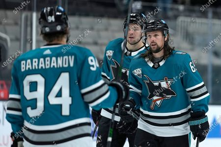 San Jose Sharks defenseman Erik Karlsson (65) is congratulated by Alexander Barabanov (94) after scoring a goal against the Arizona Coyotes during the first period of an NHL hockey game, in San Jose, Calif
