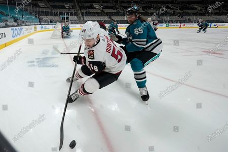 Stock Picture of Arizona Coyotes left wing Michael Bunting (58) reaches for the puck next to San Jose Sharks defenseman Erik Karlsson (65) during the second period of an NHL hockey game, in San Jose, Calif
