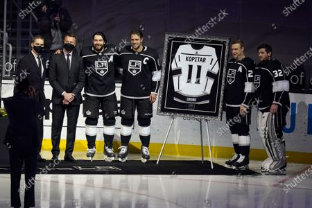 Los Angeles Kings center Anze Kopitar, center, poses for pictures with, from left, team president Luc Robitaille, general manager Rob Blake, defenseman Drew Doughty, right wing Dustin Brown and goaltender Jonathan Quick as Kopitar is honored for his 100th career point before an NHL hockey game against the Colorado Avalanche, in Los Angeles