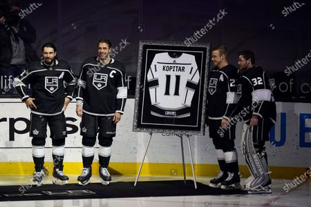 Los Angeles Kings center Anze Kopitar, center, poses for pictures with defenseman Drew Doughty, left, right wing Dustin Brown, second from right, and goaltender Jonathan Quick as Kopitar is honored for his 100th career point before an NHL hockey game against the Colorado Avalanche, in Los Angeles
