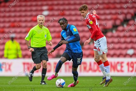 Admiral Muskwe (#15) of Wycombe Wanderers FC runs past Connor Malley (#46) of Middlesbrough FC, as referee Martin Atkinson watches on during the EFL Sky Bet Championship match between Middlesbrough and Wycombe Wanderers at the Riverside Stadium, Middlesbrough