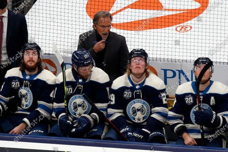 Columbus Blue Jackets coach John Tortorella is seen behind Blue Jackets players defenseman Ryan MacInnis, left, forward Kevin Stenlund, forward Patrik Laine and forward Cam Atkinson during an NHL hockey game against the Detroit Red Wings in Columbus, Ohio, . The Red Wings won 5-2