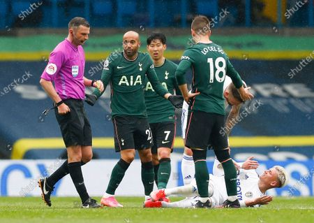 Tottenham's Lucas Moura, second left, reacts as he is booked by referee Michael Oliver, left, during the English Premier League soccer match between Leeds United and Tottenham Hotspur at Elland Road in Leeds, England