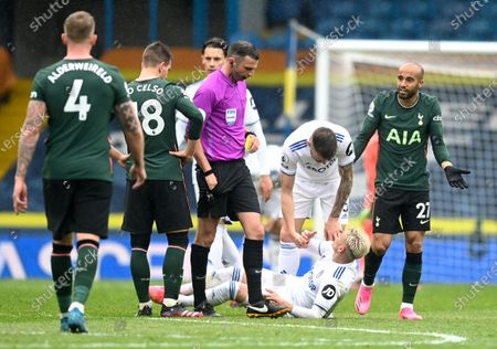 Tottenham's Lucas Moura, right, reacts as he is booked by referee Michael Oliver during the English Premier League soccer match between Leeds United and Tottenham Hotspur at Elland Road in Leeds, England