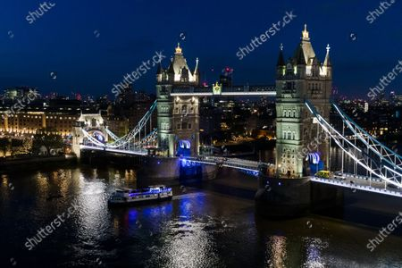 A boat travels under Tower Bridge at night seen from City Hall on the evening that the Mayor of London, Sadiq Khan, was re-elected as the Mayor of London, at City Hall in London, Britain, 08 May 2021. Britons voted on 06 May 2021 in local and mayoral elections.