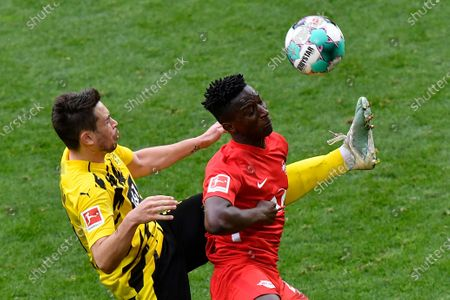 Dortmund's Raphael Guerreiro, left, fights for the ball with Leipzig's Amadou Haidara during the German Bundesliga soccer match between Borussia Dortmund and RB Leipzig in Dortmund, Germany