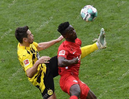 Dortmund's Raphael Guerreiro (L) in action against Leipzig's Amadou Haidara (R) during the German Bundesliga soccer match between Borussia Dortmund and RB Leipzig in Dortmund, Germany, 08 May 2021.