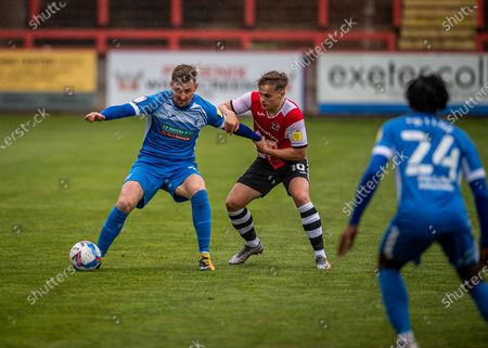 Stock Image of Barrow Forward Scott Quigley (9) battles for the ball and shields the ball from Exeter City Midfielder Archie Collins (10)  during the EFL Sky Bet League 2 match between Exeter City and Barrow at St James' Park, Exeter