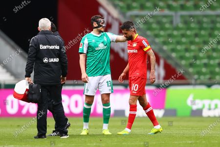 Kerem Demirbay of Bayer Leverkusen is consoled by Milos Veljkovic of Werder Bremen as he walks off the pitch after an injury during the Bundesliga match between SV Werder Bremen and Bayer 04 Leverkusen at Wohninvest Weserstadion in Bremen, Germany, 08 May 2021.