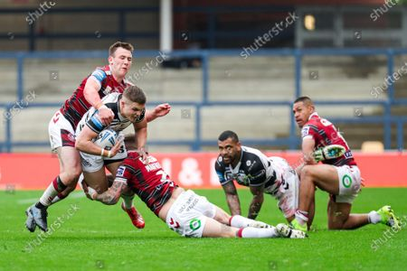 Hull FC's Cameron Scott is tackled by Wigan's Dom Manfredi and Harry Smith.