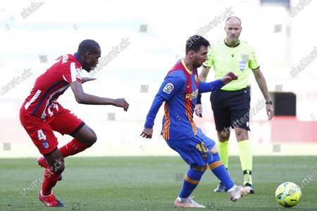 Barcelona's Lionel Messi, right, is challenged by Atletico Madrid's Geoffrey Kondogbia during the Spanish La Liga soccer match between FC Barcelona and Atletico Madrid at the Camp Nou stadium in Barcelona, Spain