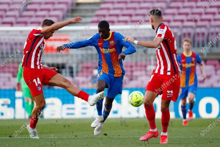 Barcelona's Ousmane Dembele, center, is challenged by Atletico Madrid's Marcos Llorente, left, and Atletico Madrid's Yannick Carrasco during the Spanish La Liga soccer match between FC Barcelona and Atletico Madrid at the Camp Nou stadium in Barcelona, Spain