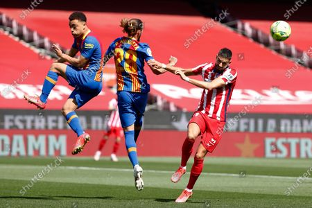 Atletico Madrid's Yannick Carrasco, right, attempts a shot at goal in front of Barcelona's Sergino Dest, left, and Barcelona's Oscar Mingueza during the Spanish La Liga soccer match between FC Barcelona and Atletico Madrid at the Camp Nou stadium in Barcelona, Spain