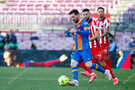 Barcelona's Lionel Messi, left, runs with the ball past Atletico Madrid's Yannick Carrasco during the Spanish La Liga soccer match between FC Barcelona and Atletico Madrid at the Camp Nou stadium in Barcelona, Spain