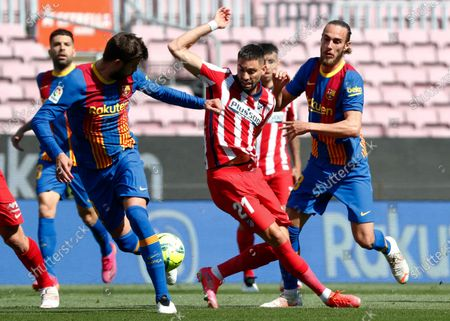 Atletico Madrid's Yannick Carrasco, center, fights for the ball with Barcelona's Gerard Pique, left, and Barcelona's Oscar Mingueza during the Spanish La Liga soccer match between FC Barcelona and Atletico Madrid at the Camp Nou stadium in Barcelona, Spain