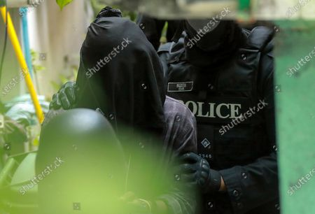 Maldives Police personnel lead a hooded and cuffed suspected terrorist into custody in connection with the recent blast in Male, Maldives 08 May 2021. Maldives former president and current parliament speaker Mohamed Nasheed was injured in a blast outside his family home on 06 May and admitted to hospital in critical condition.
