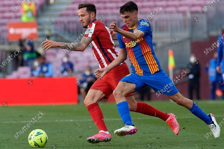 """Saul Niguez of Atletico Madrid and Pedro Gonzalez """"Pedri"""" of Barcelona compete for the ball during the La Liga Santander match between FC Barcelona and Atletico de Madrid at Camp Nou on May 8, 2021 in Barcelona, Spain. Sporting stadiums around Spain remain under strict restrictions due to the Coronavirus Pandemic as Government social distancing laws prohibit fans inside venues resulting in games being played behind closed doors."""