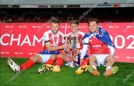 Andy Williams, George Lloyd and Finn Azaz of Cheltenham Town pose with the trophy after winning the league